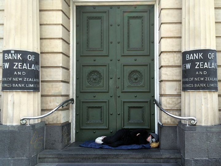 a homeless person sleep on the steps of a bank in new zealand in 2015.