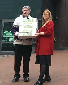 Mark Beale hands the petition to Green MP Denise Roche.