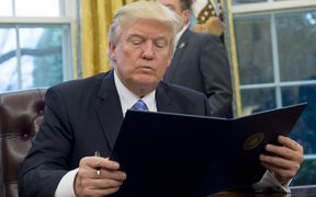 US President Donald Trump reads an executive order withdrawing the US from the Trans-Pacific Partnership prior to signing it in the Oval Office of the White House.