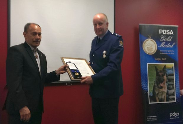 Senior Constable Lamb receives the PDSA gold medal for Gage.