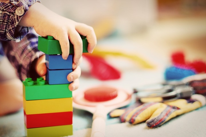 Kid playing with coloured blocks