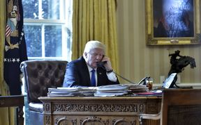 Donald Trump on the telephone in the Oval Office of the White House.