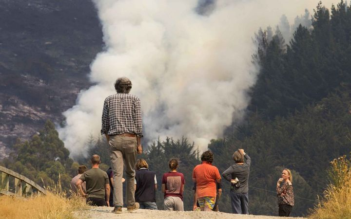 Locals watch one of the fires on the Port Hills.