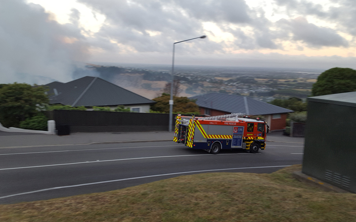 A fire engine speeds through Christchurch as smoke billows from the Port Hills fire.