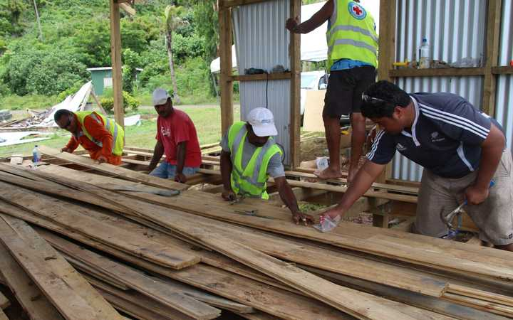 Workers lay the floor for a new disaster shelter on Koro island