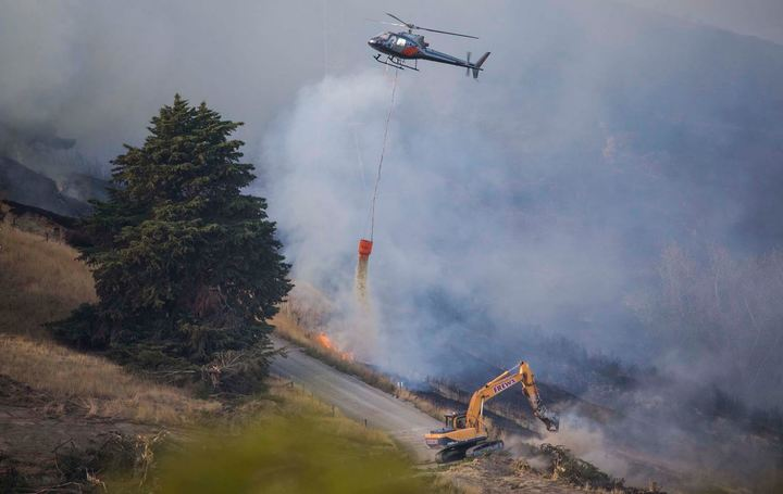 Helicopters and heavy earth-moving equipment are part of the fire response.