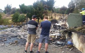 Simon Grace at the remains of his home with his brother.
