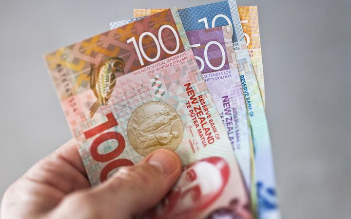 New Zealand currency held fanned out in someones hand