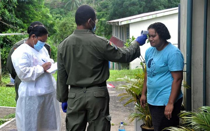 A soldier helps mobile screening teams carry out door-to-door tests in Suva.