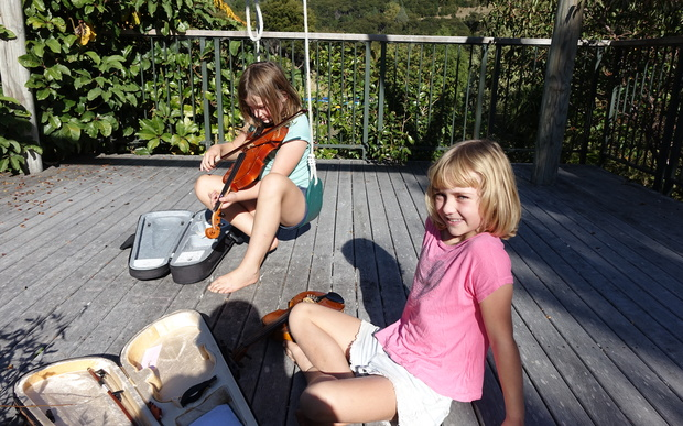 Isabelle and Sophie play their violins to attract the tui which seems to work