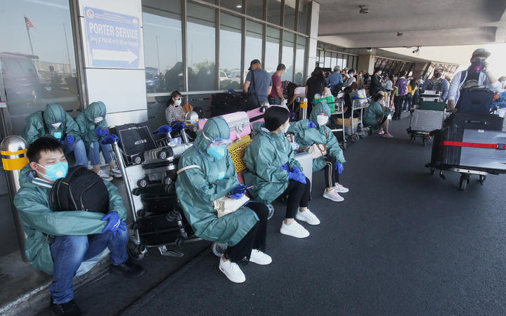 Passengers in protective gear sit on the pavement as they wait for their flights out of the country at Manila's international airport on March 19, 2020.