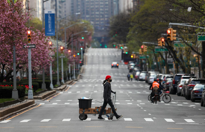 NEW YORK, USA - APRIL 12: An amazon delivery person, with a face mask, crosses a street on Park Avenue, remaining nearly empty due to coronavirus (COVID-19) pandemic in New York City, United States, on April 12, 2020. Tayfun Coskun / Anadolu Agency