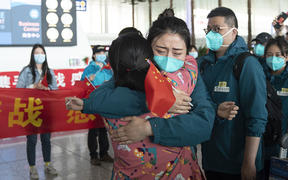 A medical worker from the Peking Union Medical College Hospital bids farewell to a local medical worker at the Wuhan Tianhe International Airport in Wuhan, capital of central China's Hubei Province, April 15, 2020.