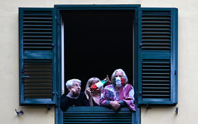 People with protective masks look from their windows at artists performing for the show Sotto lo Stesso Cielo tour (Under the Same Sky tour) in Rome on 18 April 2020.