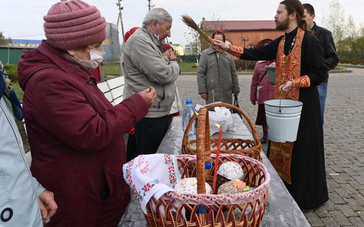 An orthodox priest blesses Easter cakes and eggs with holy water during Easter celebrations at Krasnodar region, Russia.  Sergey Pivovarov / Sputnik
