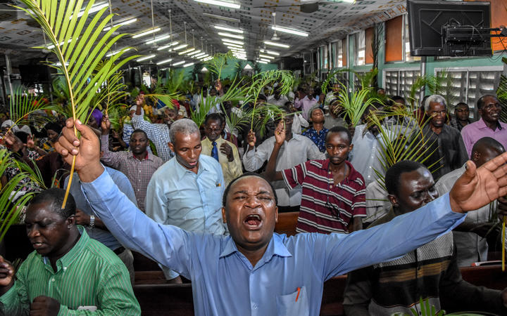 Believers pray without taking social distancing during a Palm Sunday mass at the Full Gospel Bible Fellowship Church in Dar es Salaam, Tanzania, on April 5, 2020