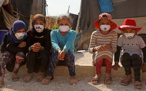 Displaced Syrian girls wear face masks decorated by artists during a COVID-19 awareness campaign at the Bardaqli camp in the town of Dana in Syria's northwestern Idlib province, on April 20, 2020.
