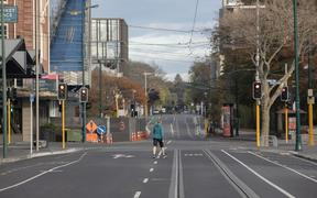A woman walks across an empty intersection in Christchurch, New Zealand, on April 16, 2020. New Zealand is currently in alert level four.