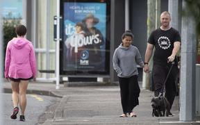 Pedestrians practise social distancing in response to the COVID-19 coronavirus outbreak along a street of Lower Hutt, near Wellington, on April 20, 2020.