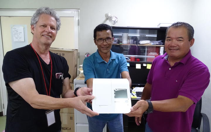 Marshall Islands Health Secretary Jack Niedenthal, left, joins Majuro hospital laboratory director Paul Lalita and Dr. Robert Maddison in showing Covid-19 test equipment