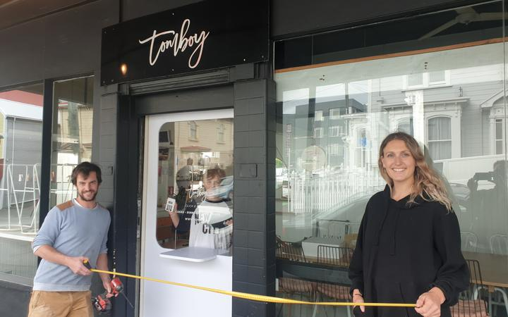 Tomboy cakery and café owner Kate Marinkovich tries out her new door which will her to to do contactless pickup.