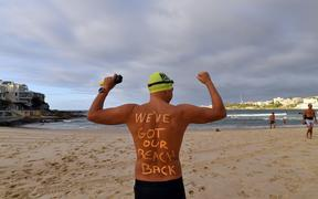 A man poses with a message on his back before enjoying his first swim after Bondi Beach reopened following a five week closure in Sydney on April 28, 2020.