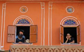 Residents look out from window at walled city during the nationwide Lockdown imposed in the wake of the deadly novel coronavirus pandemic  in Jaipur, Rajasthan,India.