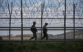 South Korean soldiers patrol along a barbed wire fence Demilitarized Zone (DMZ) separating North and South Korea, on the South Korean island of Ganghwa on April 23, 2020.