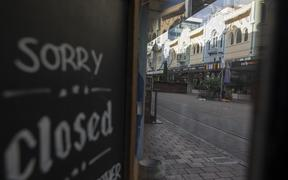 A closure sign is displayed on a shop in an empty street in Christchurch, New Zealand, on April 16, 2020.