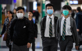 Young students wear face masks in the arrivals hall at Hong Kong's international airport on January 22, 2020.