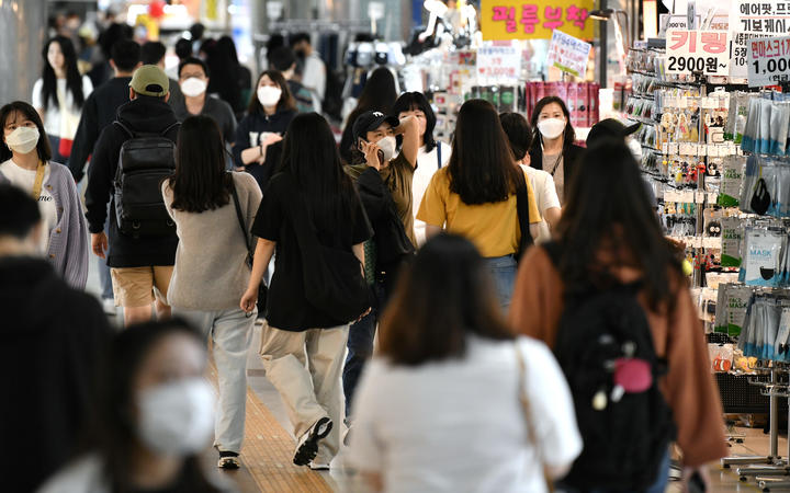 People wearing face masks walk through an underground shopping area in Seoul on May 6, 2020.