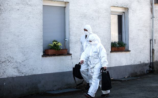 Members of the crime scene unit walking past the house of the accused couple in Hoexter, Germany.