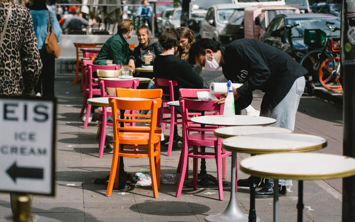 A waiter with face mask cleans the tables outside of a cafe. As the state government allows all the restaurants and cafes reopen, in Cologne, Germany, on May 11, 2020.