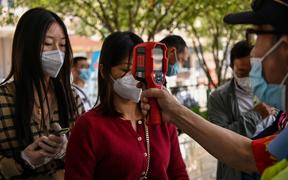 A worker wearing a face mask checks passengers body temperatures and a health code on their phones before they take a taxi after arriving at Hankou railway station in Wuhan, China's central Hubei province on May 12, 2020.