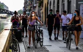 People stroll along the Navigli canals in Milan on May 8, 2020 during the country's lockdown aimed at curbing the spread of the COVID-19 infection, caused by the novel coronavirus.