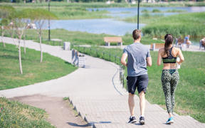 Back view portrait of modern young couple running together outdoors in city park, copy space