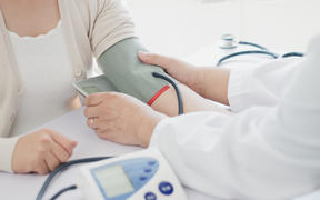 Doctor measures blood pressure of patient.