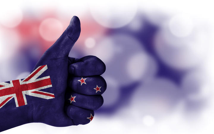 Flag of New Zealand drawn on a man's hand with a thumb up, on a blurry background with a good place for text