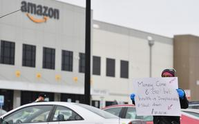 In this file photo taken on March 30, 2020 Amazon workers at Amazon's Staten Island warehouse strike in demand that the facility be shut down and cleaned after one staffer tested positive for the coronavirus in New York.