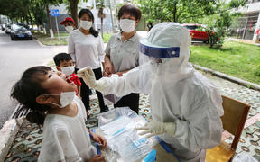 This photo taken on May 16, 2020 shows a medical worker taking a swab sample from a child to be tested for the COVID-19 coronavirus, in a street in Wuhan, in China's central Hubei province.