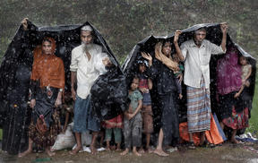Rohingya refugees shelter from the rain in a camp in Cox's Bazar, Bangladesh, September 17, 2017.
