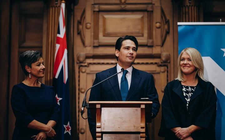 Outgoing National leader Simon Bridges, flanked by his deputy leader Paula Bennett and his wife Natalie Bridges, gives his resignation speech.