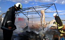 Firefighters extinguish a fire after a Syrian regime warcraft targeted the Kamuna refugee camp near the Sarmada town of Idlib province, Syria on May 05, 2016.