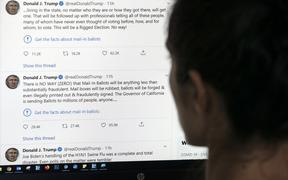 "This illustration photo shows an editor in Los Angeles looking at the official Twitter account of US President Donald Trump on May 26, 2020, with two tweets by the president under which Twitter posted a link reading ""Get the facts about mail-in ballots""."