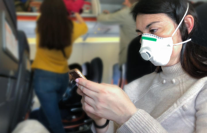 Airplane passenger with with respiratory mask looking at phone.