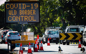 This file photo taken on April 15, 2020 shows a COVID-19 coronavirus sign at a Pacific Highway vehicle checkpoint on the Queensland-New South Wales state border near Coolangatta.