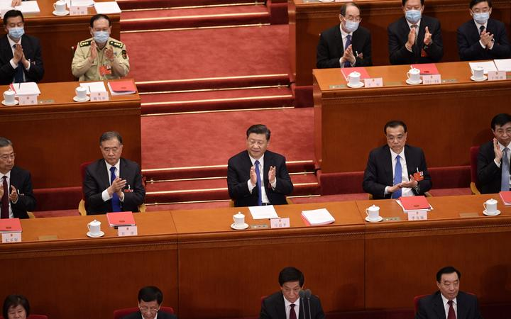 China's President Xi Jinping (centre) applauds after the vote on a proposal to draft a Hong Kong security law during the closing session of the National People's Congress at the Great Hall of the People in Beijing.