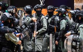 Riot police in the Central district of Hong Kong on 27 May. Police fired pepper-ball rounds and arrested hundreds as they clamped down on protests against a bill banning insults to China's national anthem.