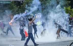 DENVER, CO - MAY 29: Protesters run from tear gas fired by police during a protest on May 29, 2020 in Denver, Colorado. This was the second day of protests in Denver