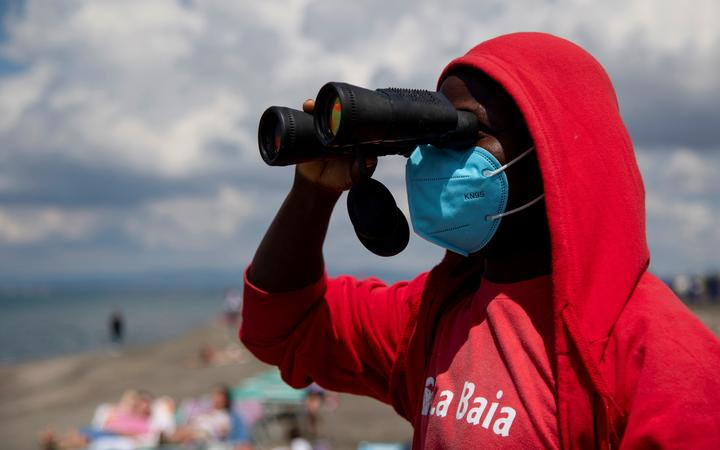 A lifeguard wearing a protective mask looks through his binoculars at a beach in Rome.